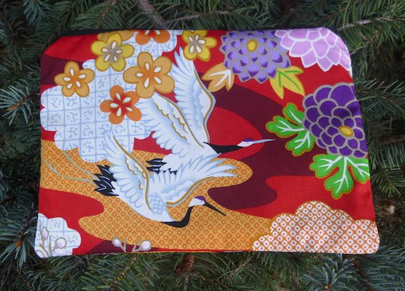 Flying Japanese cranes on red zippered makeup bag